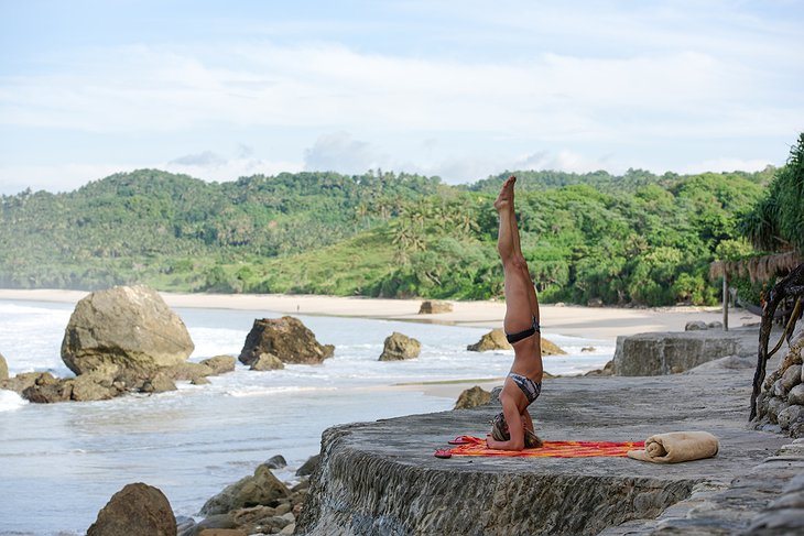 Yoga by the beach on a rock