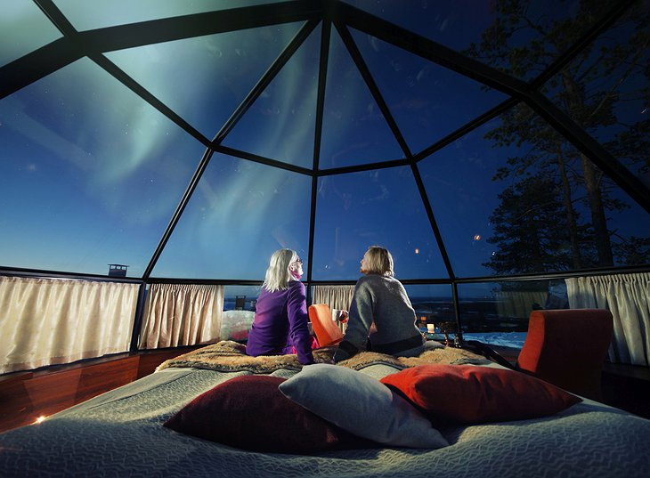 Old couple looking at the Northern Lights from the bed of their igloo at Levin Iglut