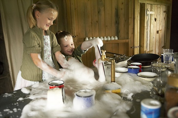 Kids washing the dishes and having fun with the foam