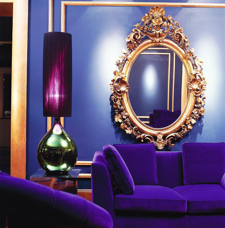Purple sofa and golden mirror