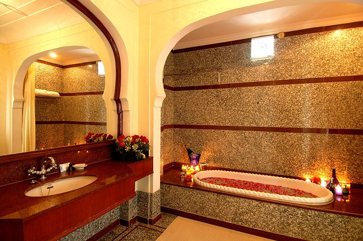The Raj Palace bathroom with tub full of flowers