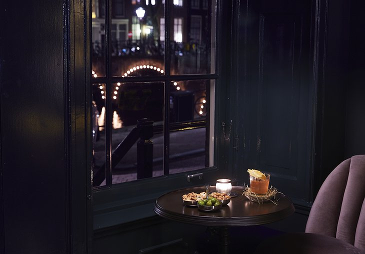 Pulitzer Amsterdam Pulitzer's Bar cozy window seat with drinks and snacks and view on the canal at night