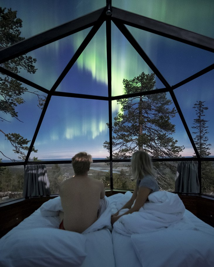 Couple in the bed in the igloo staring at the Northern Lights