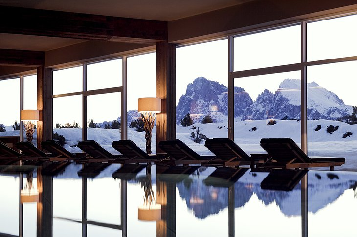 Alpina Dolomites hotel indoor swimming pool with snowy mountain view
