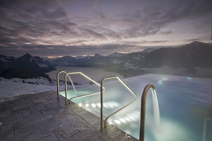 Infinity pool with snowy Alps views at night