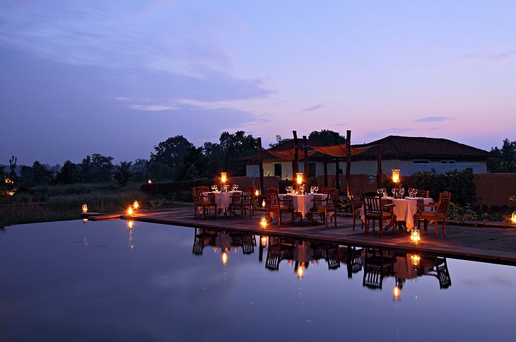 Samode Safari Lodge swimming pool in the evening with dining tables next to it