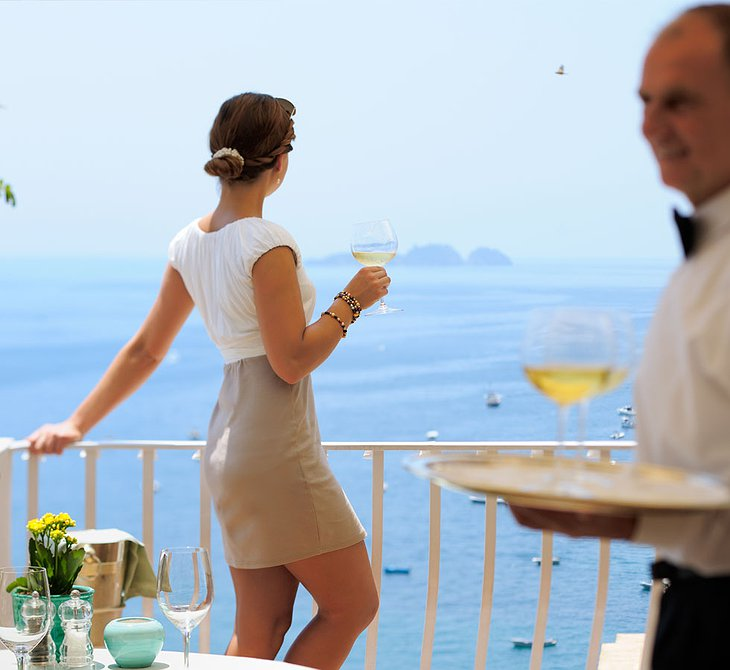 Classy woman drinking wine on the terrace of Le Sirenuse Hotel