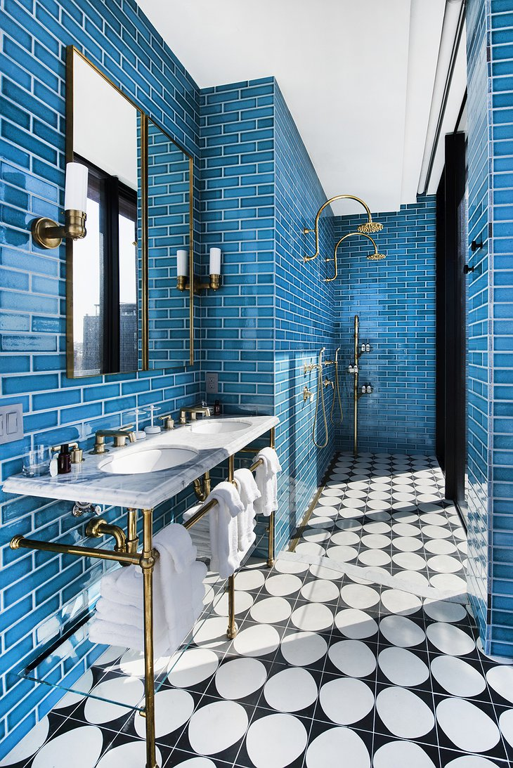 The Williamsburg Hotel bathroom with blue metro tiles and golden faucet