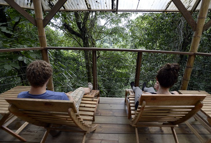 Couple on the treehouse porch overlooking the rainforest