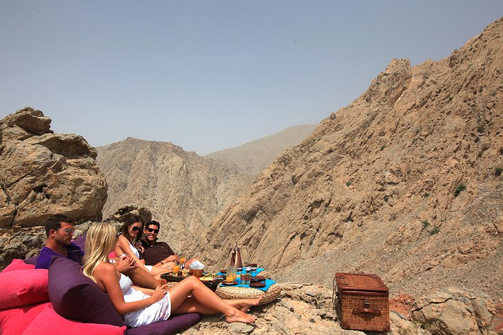 Young people dining on the rocky mountains of Oman