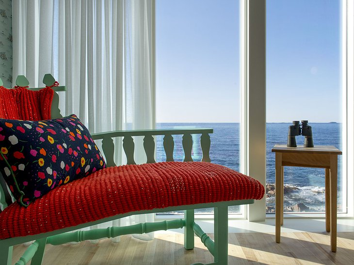 Fogo Island Inn room with green chair and panoramic sea views