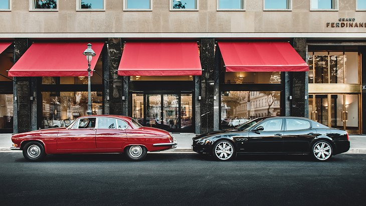 Grand Ferdinand main entrance with old-timer Jaguar and Maserati parking in front of it