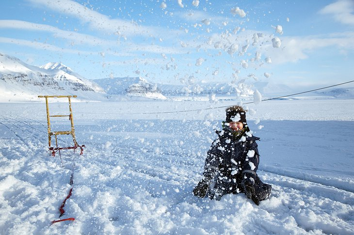 Kid enjoying the sledging on the ice of the fjord