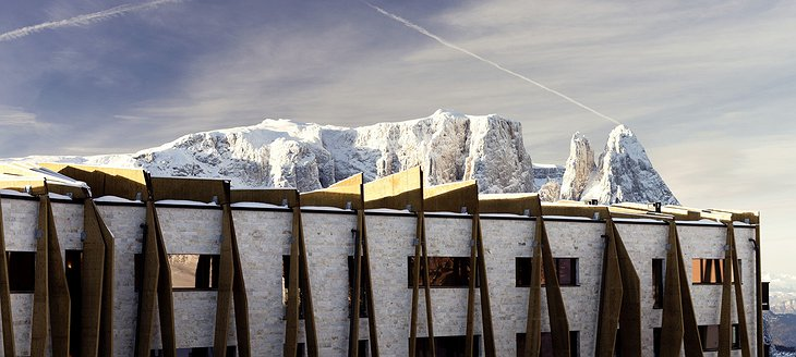Alpina Dolomites hotel facade with rock formations of the mountains the background