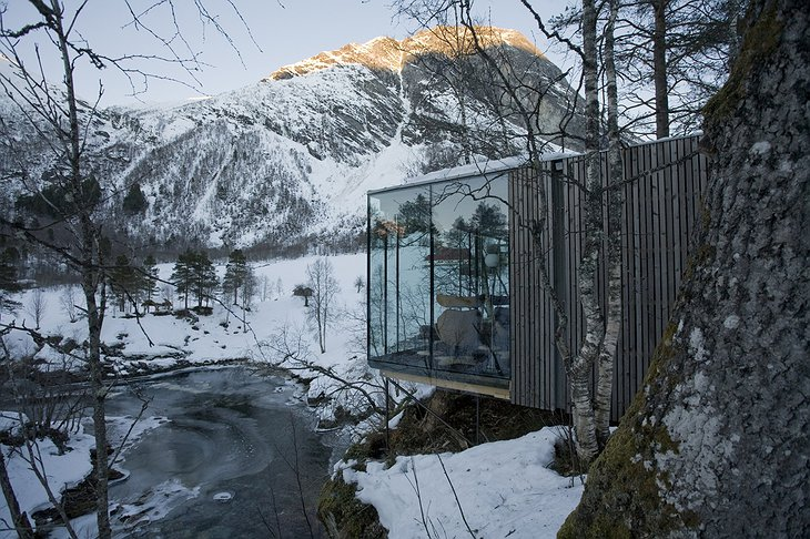 Snowy Norwegian landscape with the glass cabins of Juvet Landscape Hotel