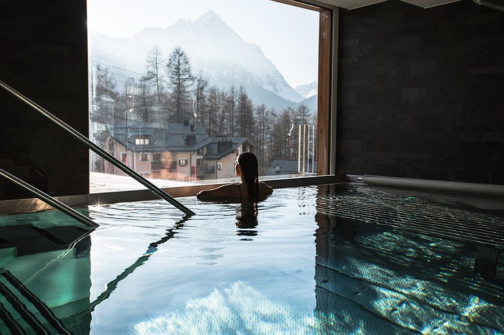 Nira Alpina whirpool with a woman inside enjoying the Alpine view