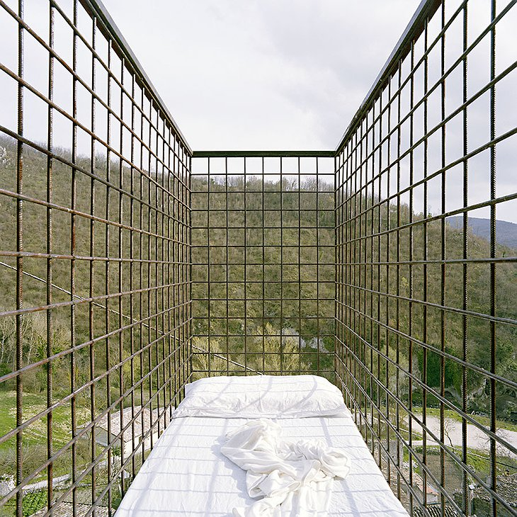 Suspended cage bed with panoramic views on forest and the stars above