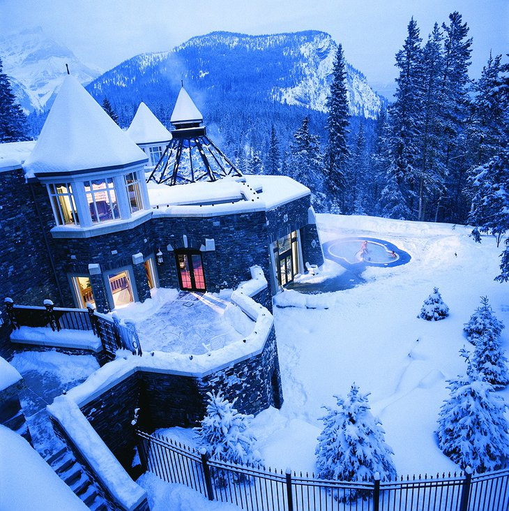 Fairmont Banff Springs Hotel during winter covered in snow and a steaming hot jacuzzi outside