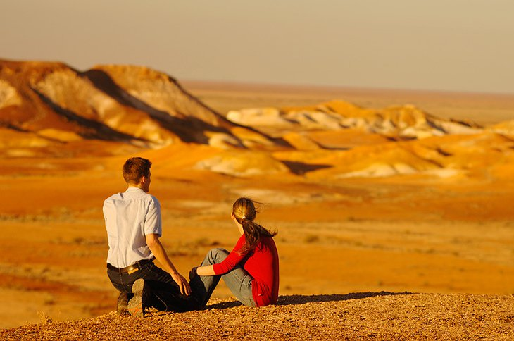 Couple sitting in the desert next to Coober Pedy in Australia