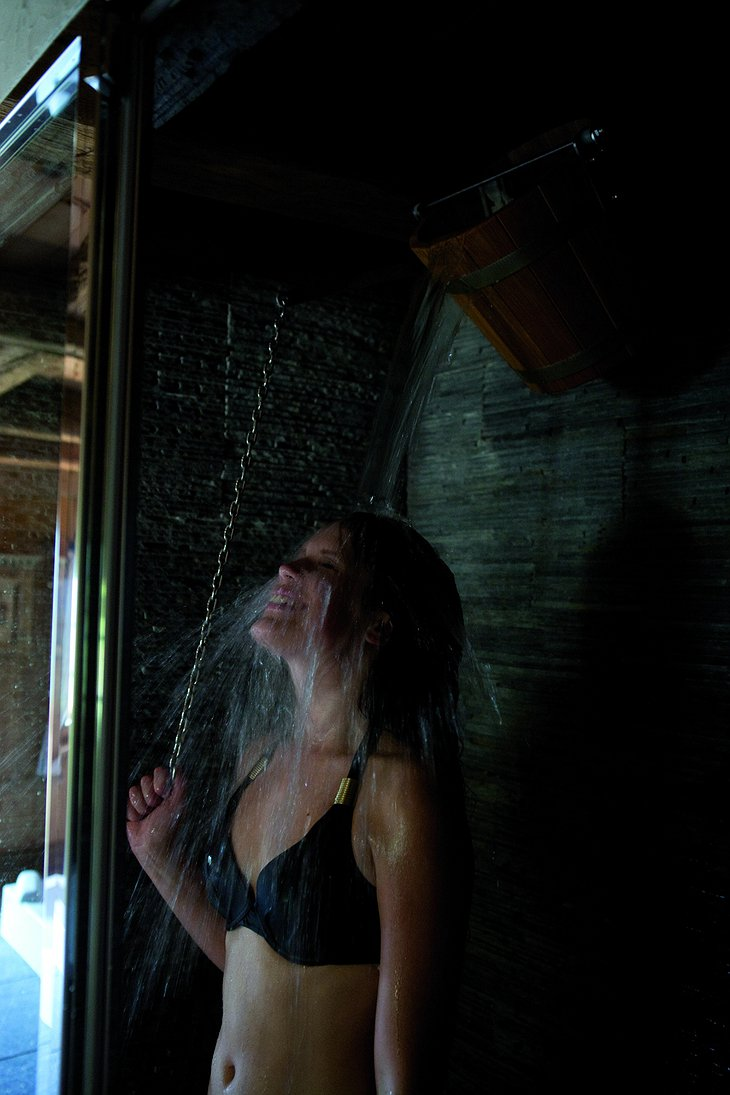 Girl using cold bucket shower after sauna