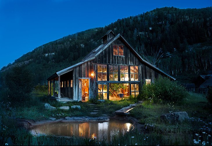 Wood cabin with large windows lit up in the night