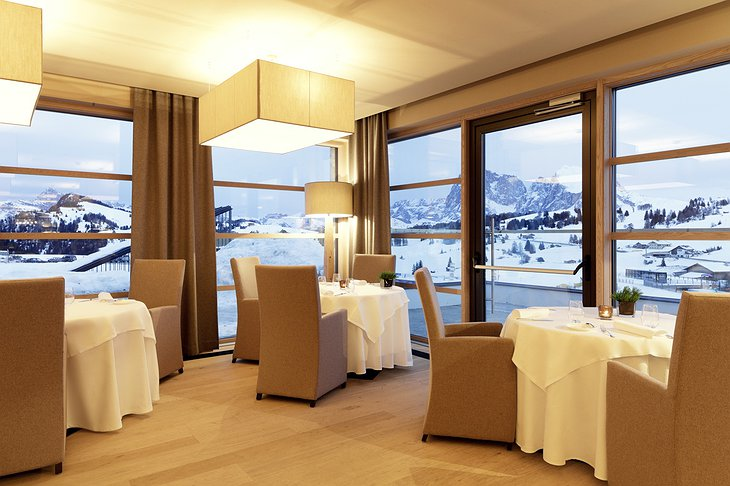 Alpina Dolomites hotel restaurant dining room with panoramic Alpine view