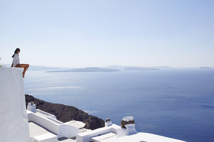 Woman sitting on top of the Kirini Santorini hotel