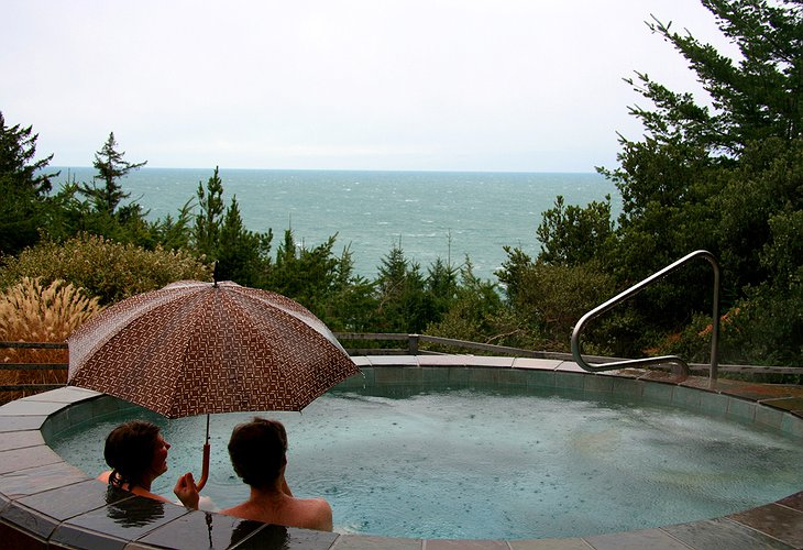 Couple under umbrella in the jacuzzi while it is raining
