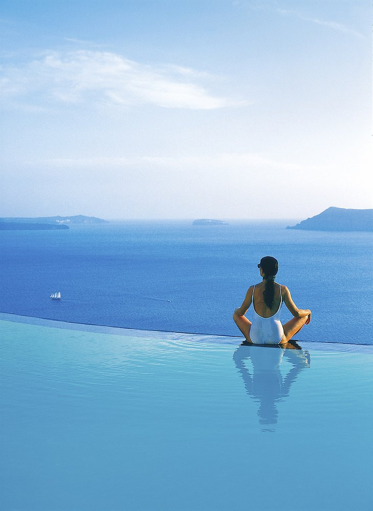 Girl sitting at the edge of the infinity pool