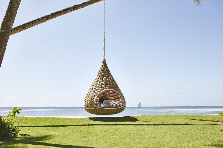 Swinging chair from palm tree on the beach