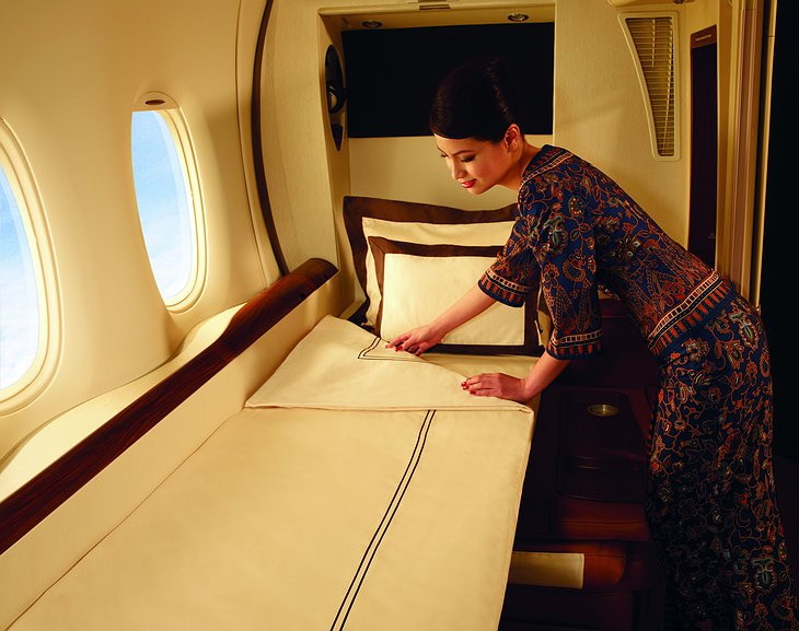 Singapore Airlines stewardess makes the bed in the luxury suite cabin