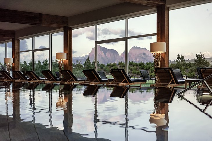 Alpina Dolomites hotel indoor swimming pool with summer mountain view