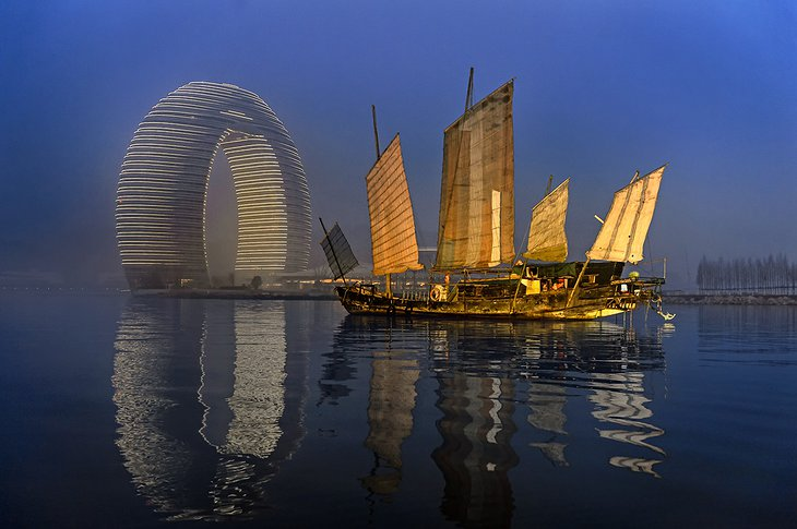 Sheraton Huzhou Hot Spring Resort at night and an old sailing boat on the sea