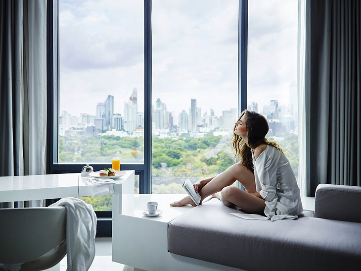 Girl sitting in the window with Bangkok view