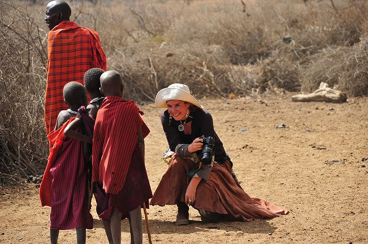 Woman interacting with kids from a Tanzanian tribe