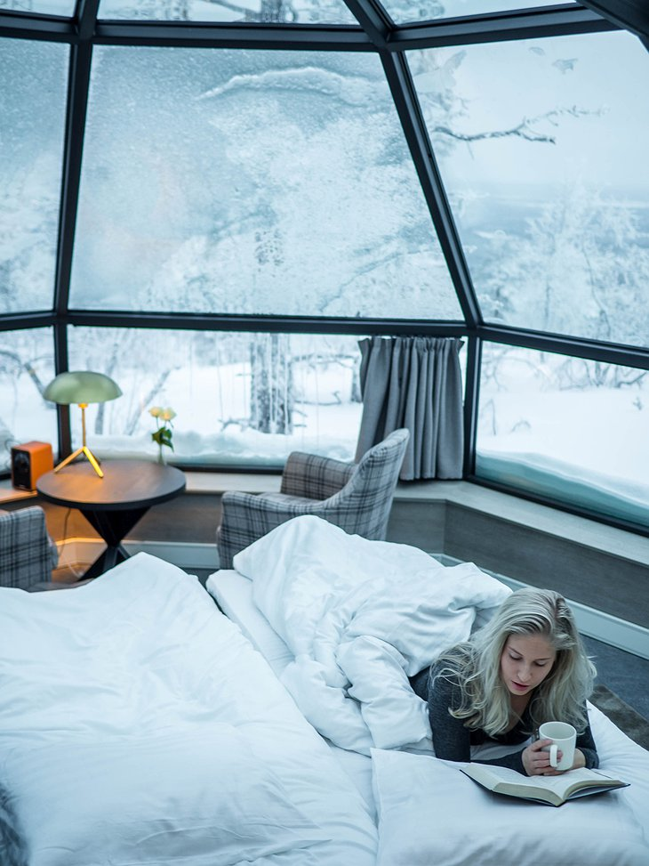 Girl reading in the bed in the igloo with snow outside
