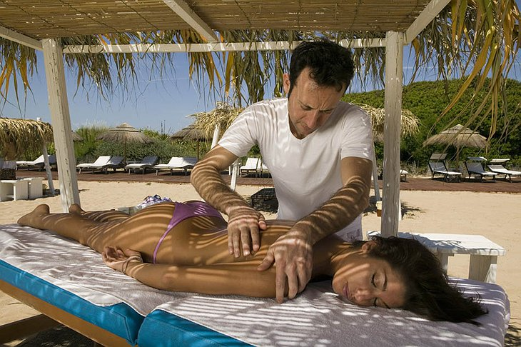 Beautiful topless girl getting a massage on the beach