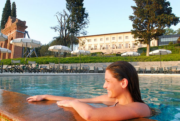 Woman smiling in the swimming pool with Fonteverde hotel in the background
