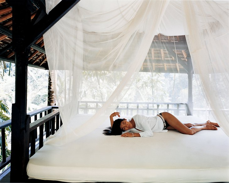 Asian girl on the white bed in an open to nature wooden room