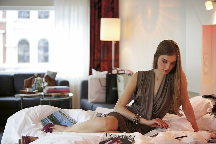 Model girl on the bed reading a newspaper